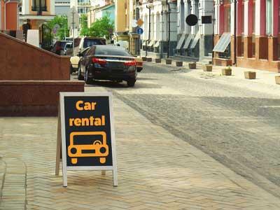 Sidewalk car rental sign