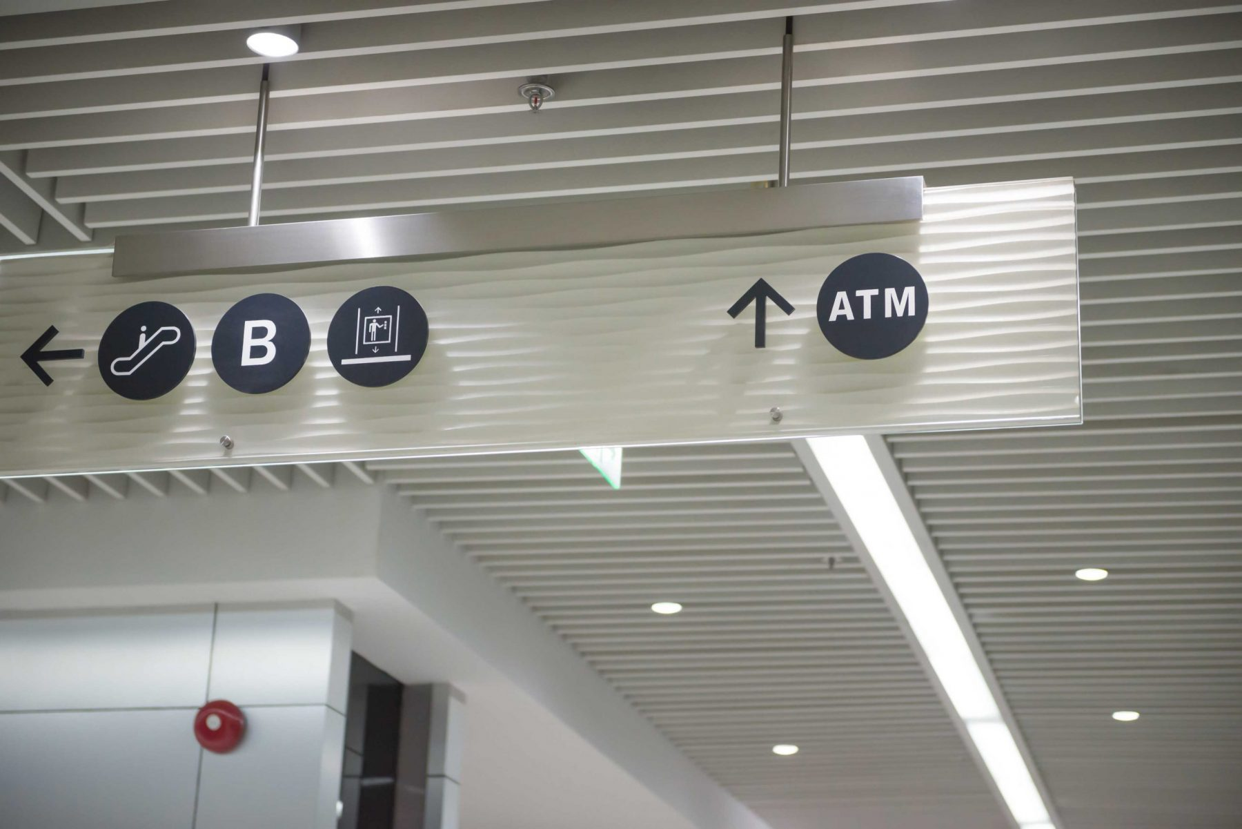 Wayfinding sign indoors to show where the elevators and atm is located