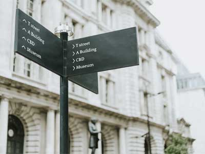 Pole sign that shows directions of different buildings