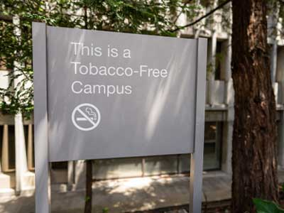 Post panel sign that states this is a tobacco free campus