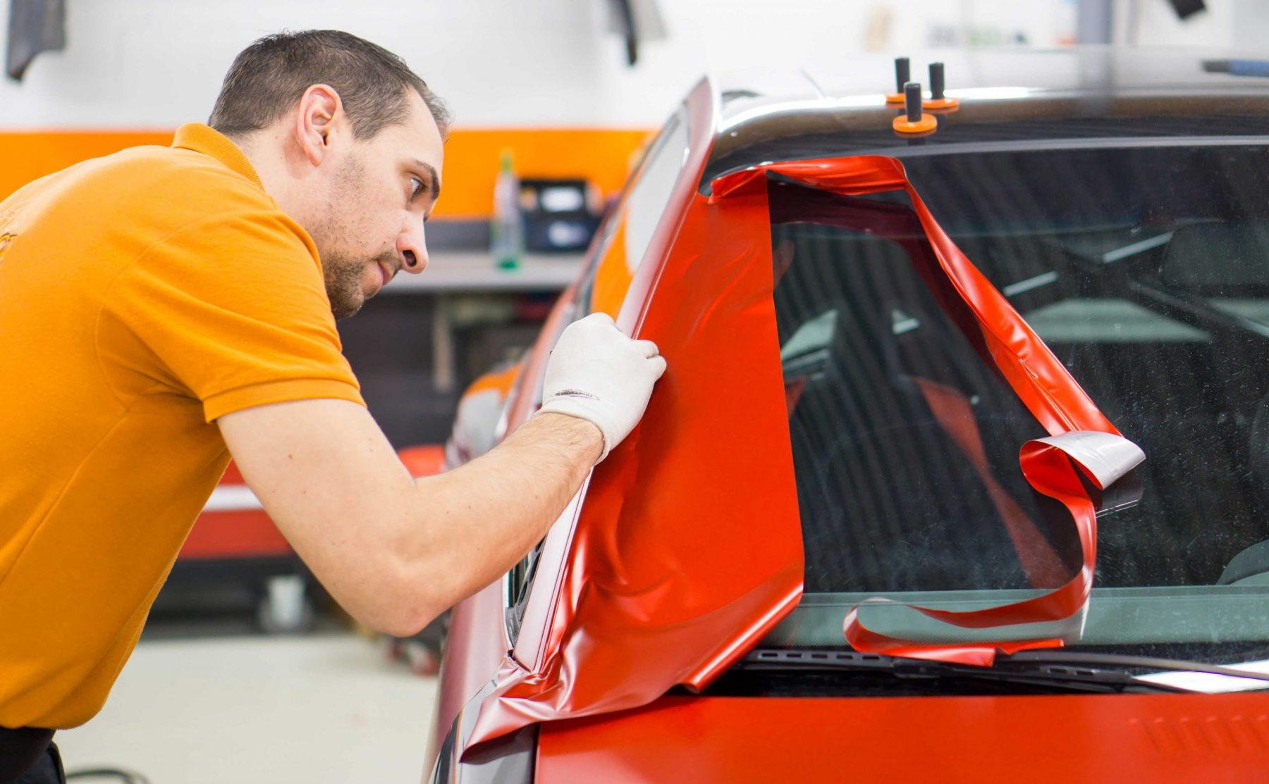 Vehicle wrap being put on a red car